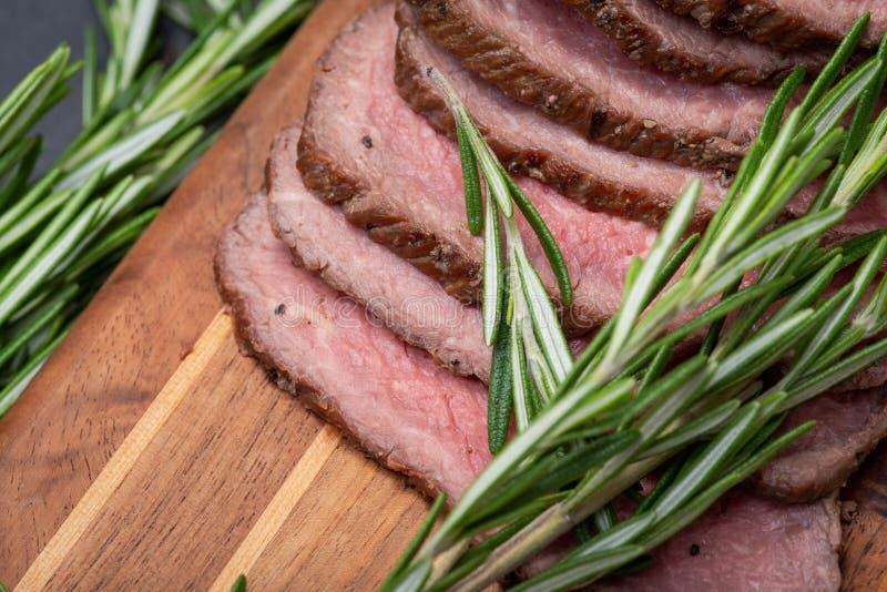 Skivat nötkött för stek för gräsFed saftigt havre som garneras med tomater, nya Rosemary Herb och regnbågepepparkorn arkivfoton
