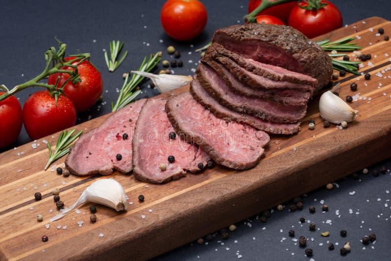 Skivat nötkött för stek för gräsFed saftigt havre som garneras med tomater, nya Rosemary Herb, vitlök- och regnbågepepparkorn arkivbild