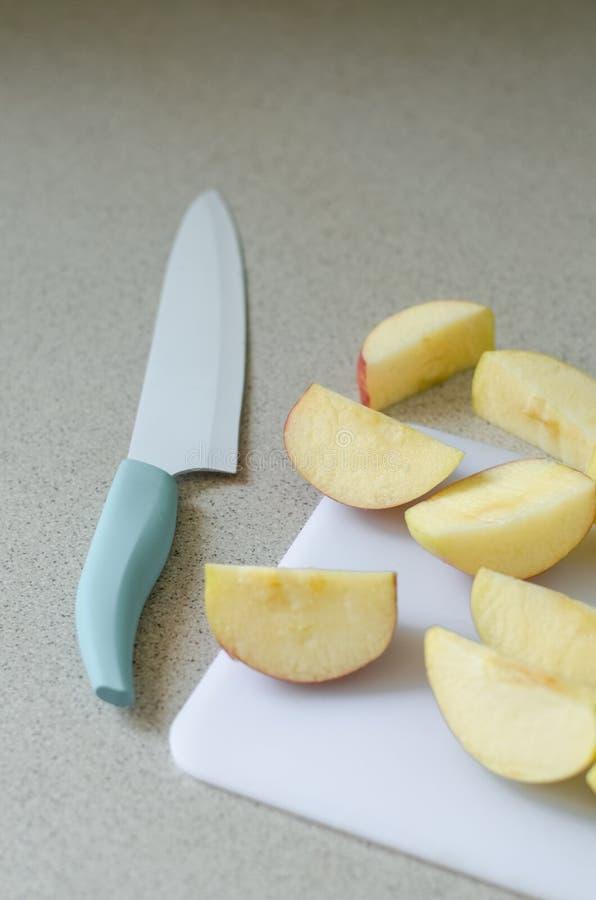 Skivat nytt äpple, kökkniv på sidan, sommarfrukt från marknaden, ingrediens för kompot royaltyfri foto