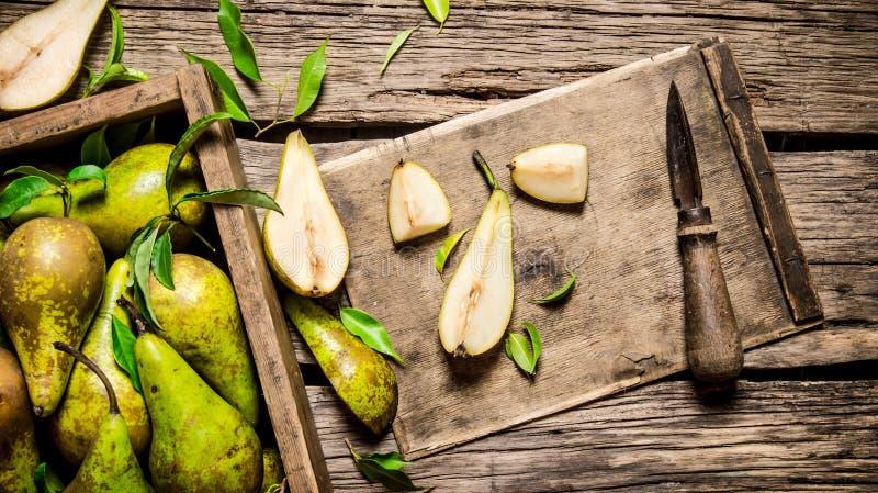 Skivat päron med kniven och sidor med en ask som är full av päron royaltyfri fotografi
