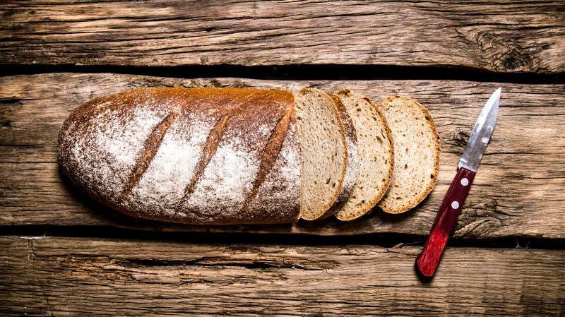 Skivat rågbröd med en kniv royaltyfria foton