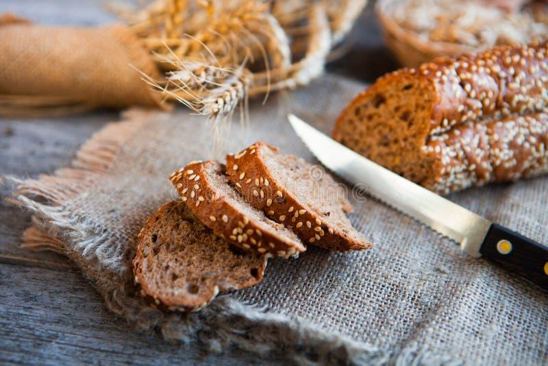 Skivat rågbröd på ett bräde På en trälantlig tabell royaltyfria bilder