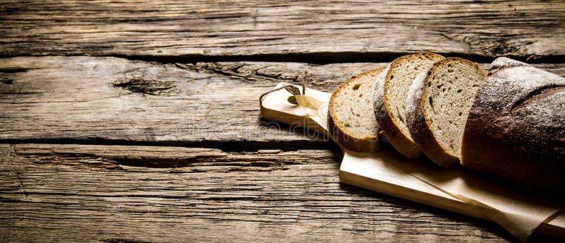 Skivat rågbröd på ett bräde trägrund tabell för djupfält royaltyfri bild