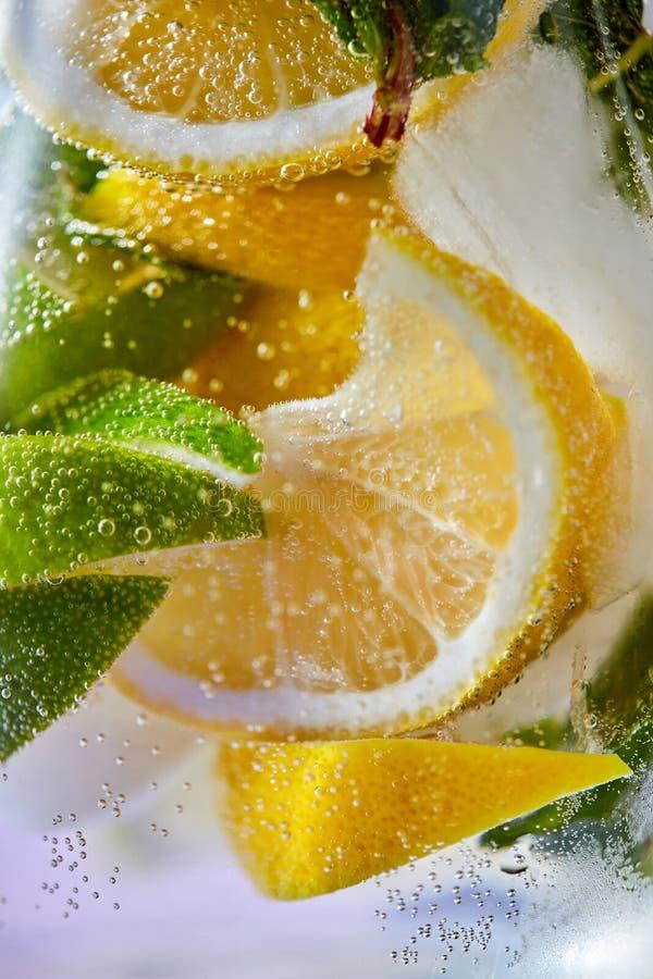 Skivor av citronen och limefrukt med bubblor av vatten i ett exponeringsglas Makrofoto av förnyande lemonad arkivfoto