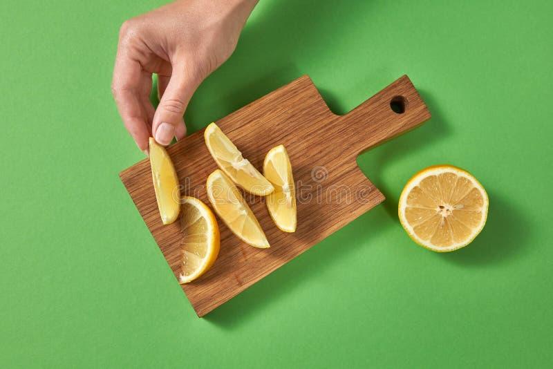Skivor av citronen på ett bräde på en grön tabell En kvinnlig hand sätter skivan av den mogna nya citronen på en träskärbräda med arkivbilder