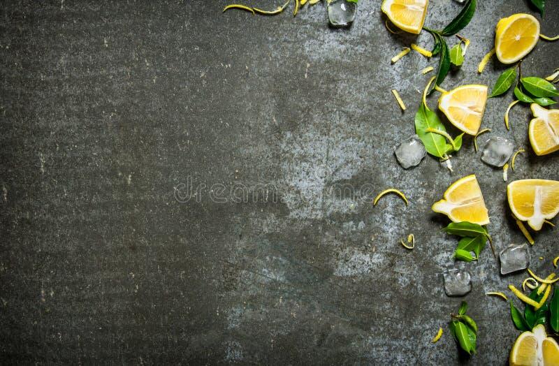 Skivor av citronen, is, sidor på stentabellen arkivfoto