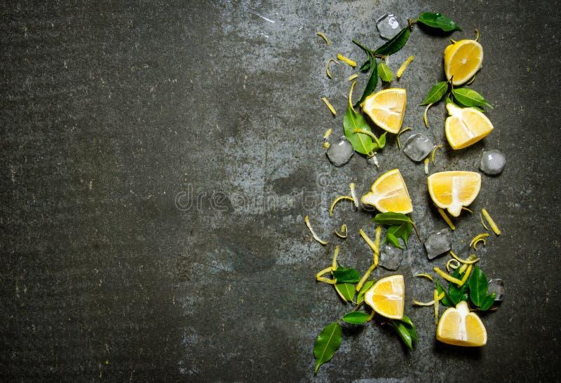 Skivor av citronen, is, sidor på stentabellen royaltyfri bild