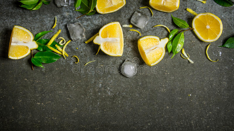 Skivor av citronen, is, sidor på stentabellen royaltyfri fotografi