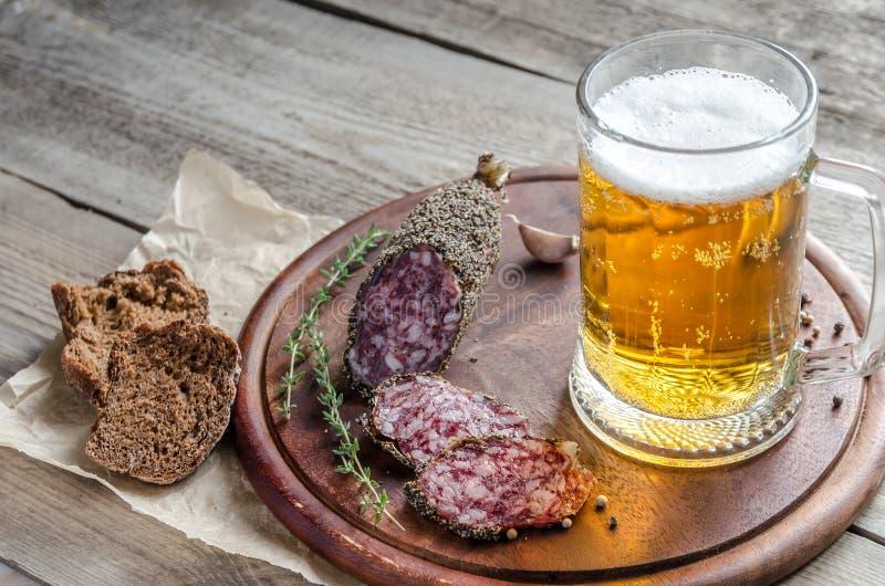 Skivor av den franska saucissonkorven med exponeringsglas av öl royaltyfria foton