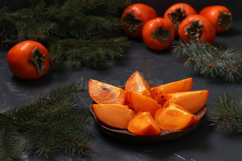 Skivor av den mogna orange persimonet är på en träplatta mot arkivbild