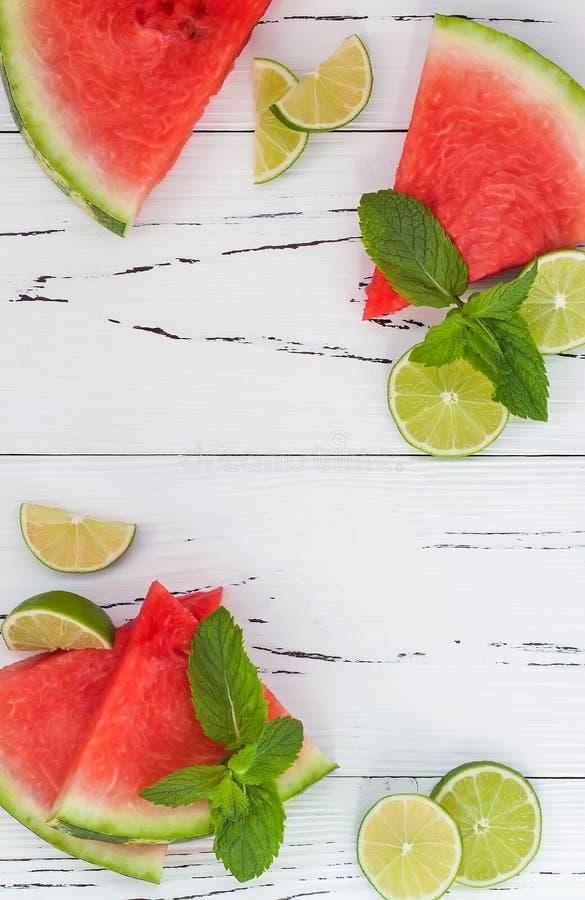 Skivor av den mogna saftiga organiska vattenmelon på den gamla trätabellen som tjänas som med nya limefrukt- och mintkaramellsido royaltyfria bilder