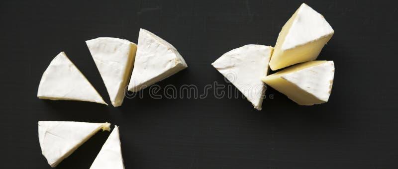 Skivor av den ostcamembert eller brien på svart yttersida Mjölka produktion Top beskådar Lekmanna- lägenhet arkivbild