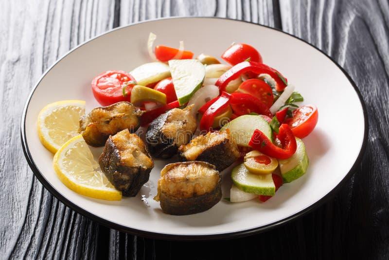Skivor av den stekte ålfisken med sallad- och citronnärbild för ny grönsak på en platta horisontal arkivfoton