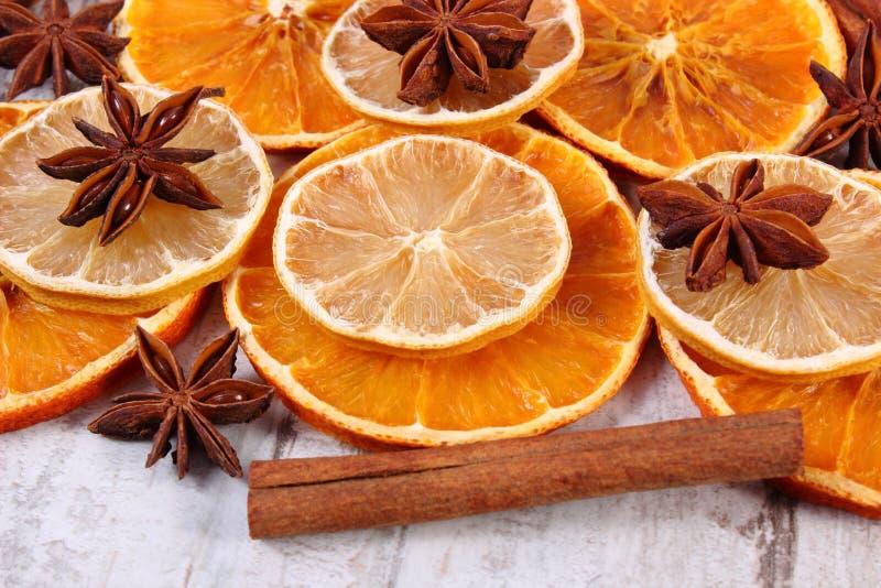 Skivor av den torkade citronen, apelsinen och kryddor på gammal träbakgrund arkivfoto
