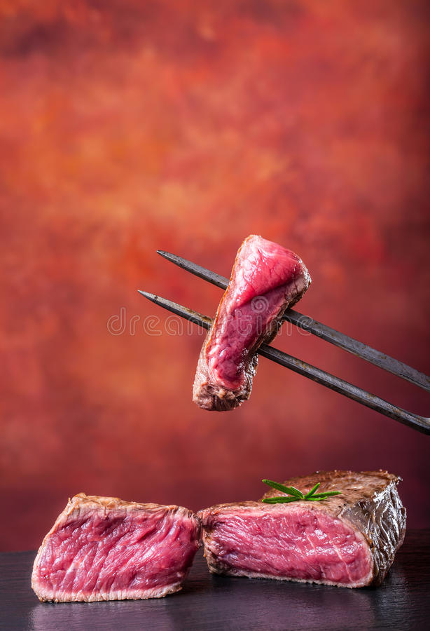 Skivor av ländstyckenötköttbiff på kött dela sig på konkret bakgrund arkivbilder