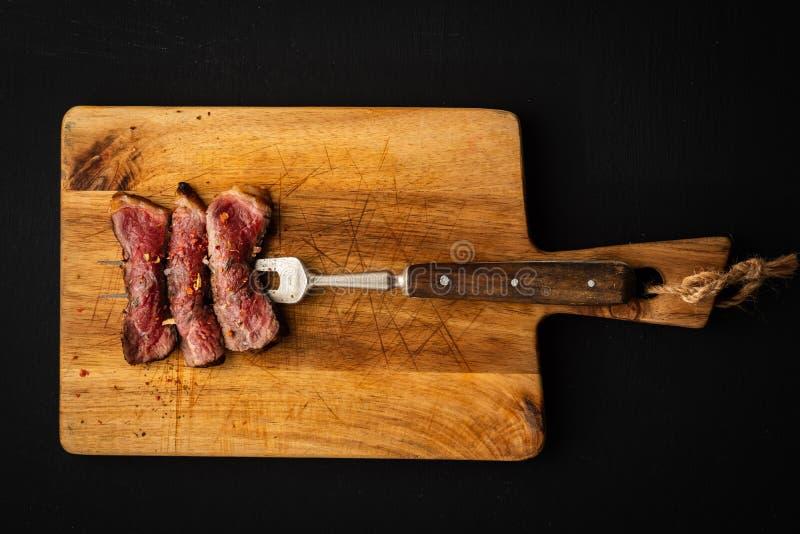 Skivor av nötköttbiff på köttgaffel på träskärbräda arkivfoton