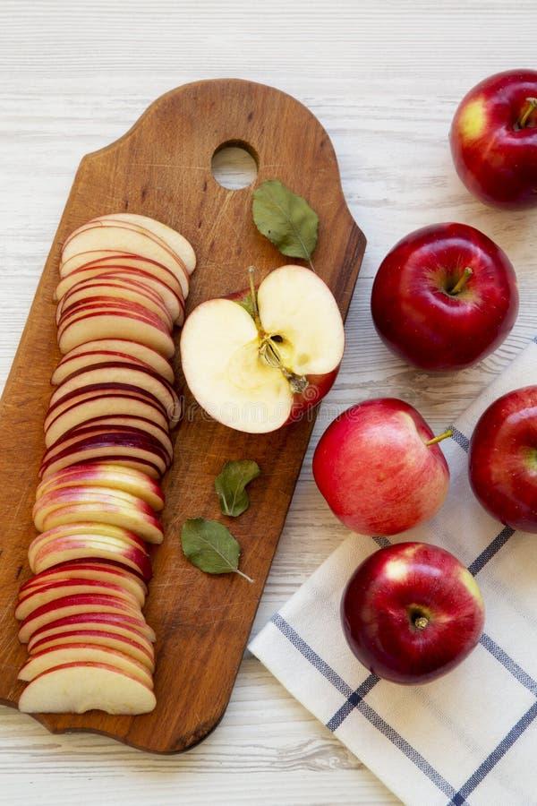 Skivor av röda äpplen på lantligt träbräde över vit träyttersida, bästa sikt Lekmanna- lägenhet, över huvudet, från över arkivbilder