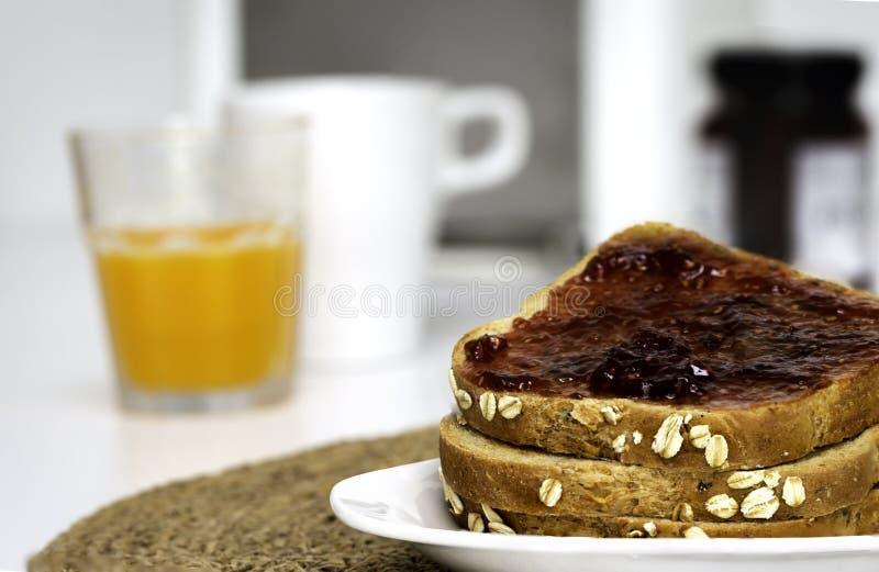 Skivor av rostat brödbröd med hemlagat jordgubbedriftstopp för frukost med unfocused bakgrund royaltyfri bild