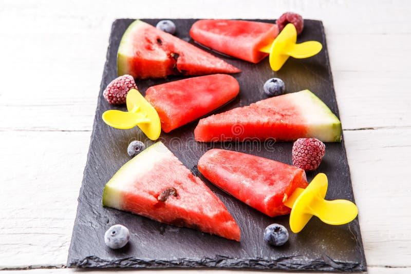 Skivor av vattenmelon, fruktis, fryste blåbär, hallon på svart bräde royaltyfri foto