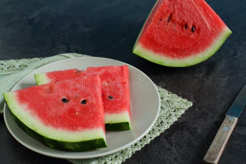 Skivor av vattenmelon på en platta på mörk bakgrund arkivbild