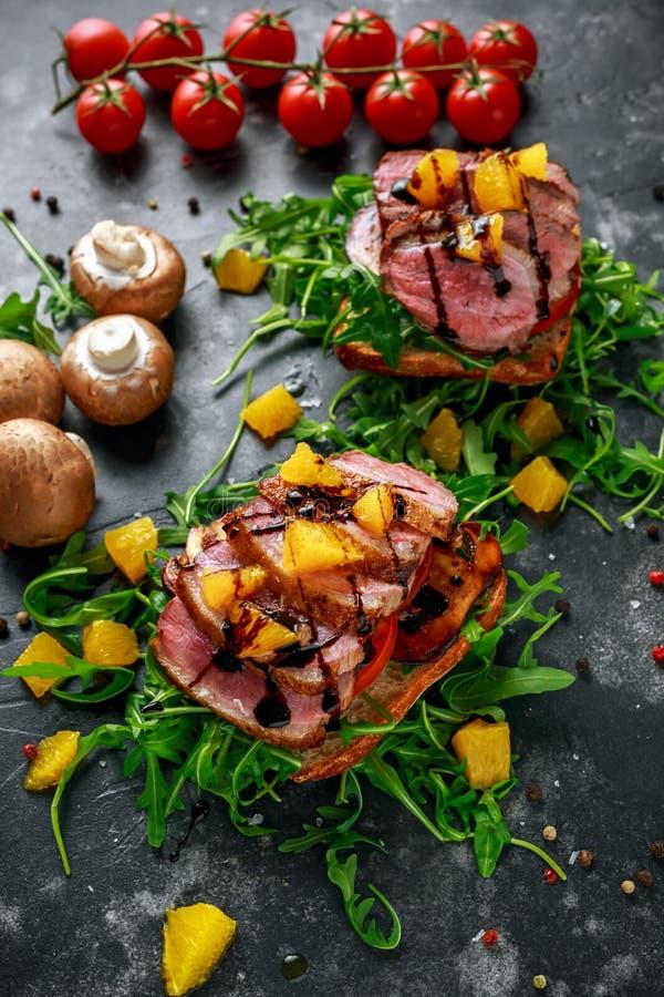 Skivor för biff för andbröst på den lösa raketkuddesmörgåsen med orange bitar, champinjoner och balsamic vinäger duggar fotografering för bildbyråer