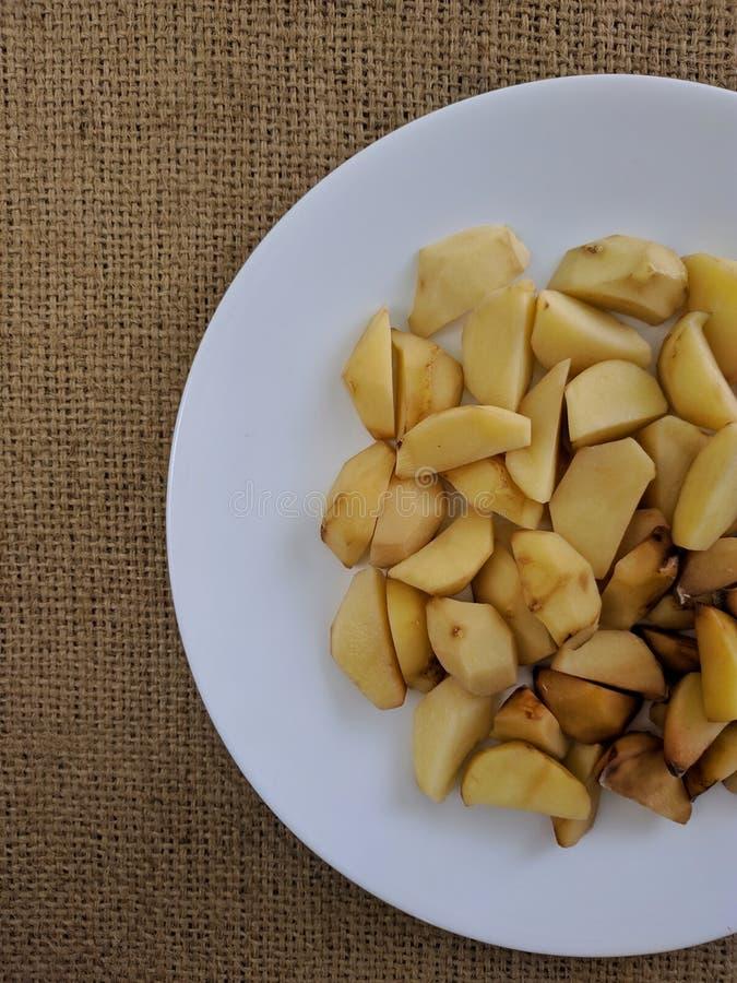 Skivor för rå potatisar på den vita plattan royaltyfri bild