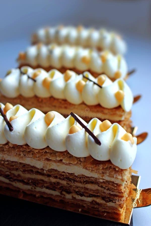 Skivor för smördegNapoleon kaka med vit toppning och citrus ostmassa på ljus bakgrund fotografering för bildbyråer