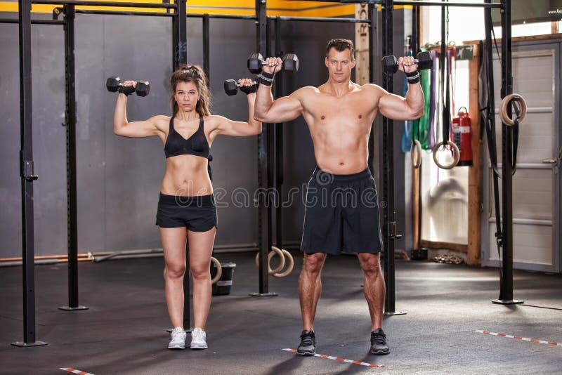 Skivstångutbildningsman och kvinna i en idrottshall royaltyfri fotografi