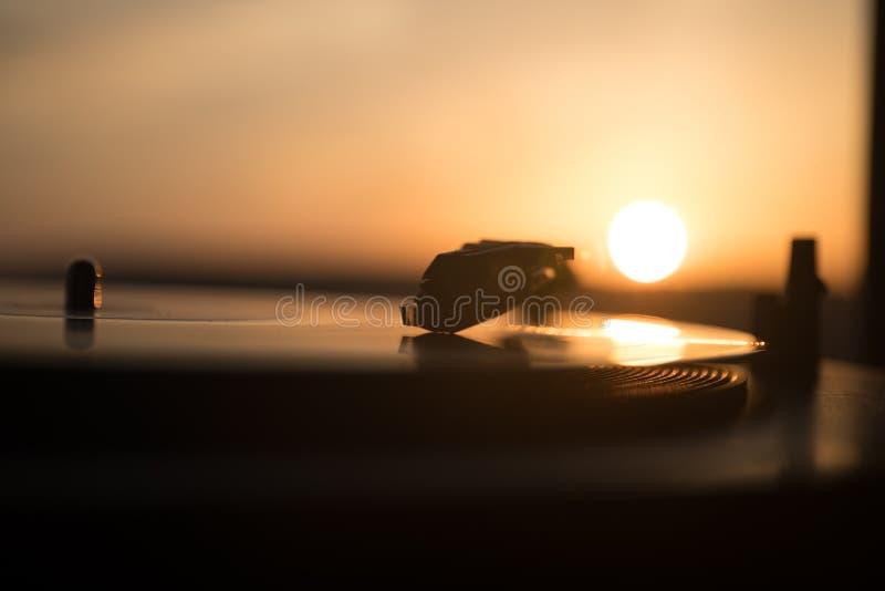 Skivtallrikvinylskivspelare på bakgrunden av en solnedgång över bergen Solid teknologi för att discjockeyn ska blanda & som spela royaltyfri foto