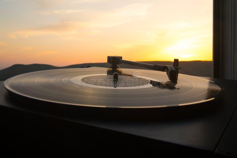Skivtallrikvinylskivspelare på bakgrunden av en solnedgång över bergen Solid teknologi för att discjockeyn ska blanda & som spela royaltyfri fotografi