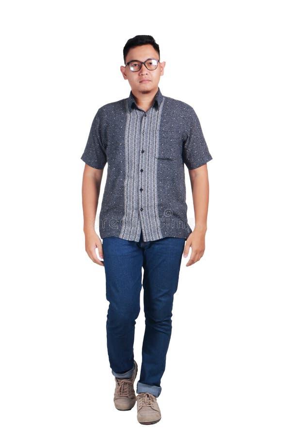 Skjorta för Batik för ungt asiatiskt mananseende bärande arkivbild