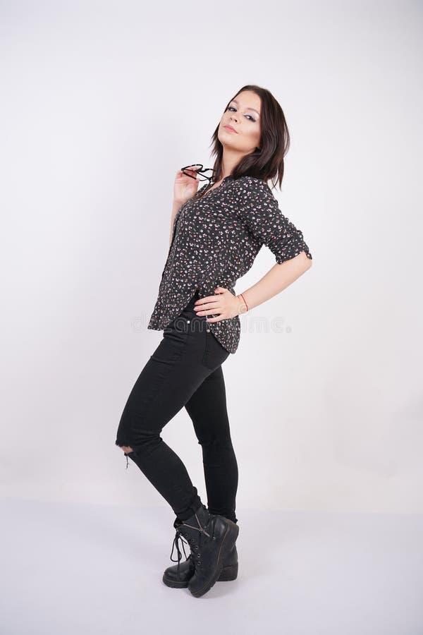 Skjorta för mode för nätt tonårig flicka bärande tillfällig och svart sönderriven jeans som poserar med glasögon på vit studiobak arkivfoton