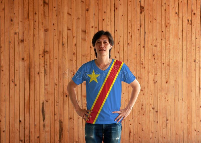 Skjorta och anseende för färg för flagga för Dr Congo för man bärande med akimbo på träväggbakgrunden royaltyfria bilder