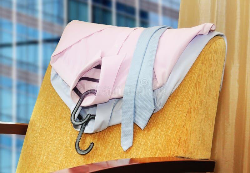 Skjorta och band som hänger på en stol arkivfoto