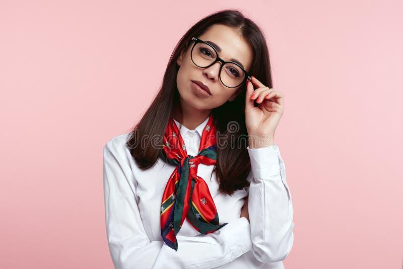 Skjorta och halsduk för ung säker brunettaffär som kvinnlig bärande vit rymmer hennes glasögon isolerat över rosa bakgrund royaltyfria bilder
