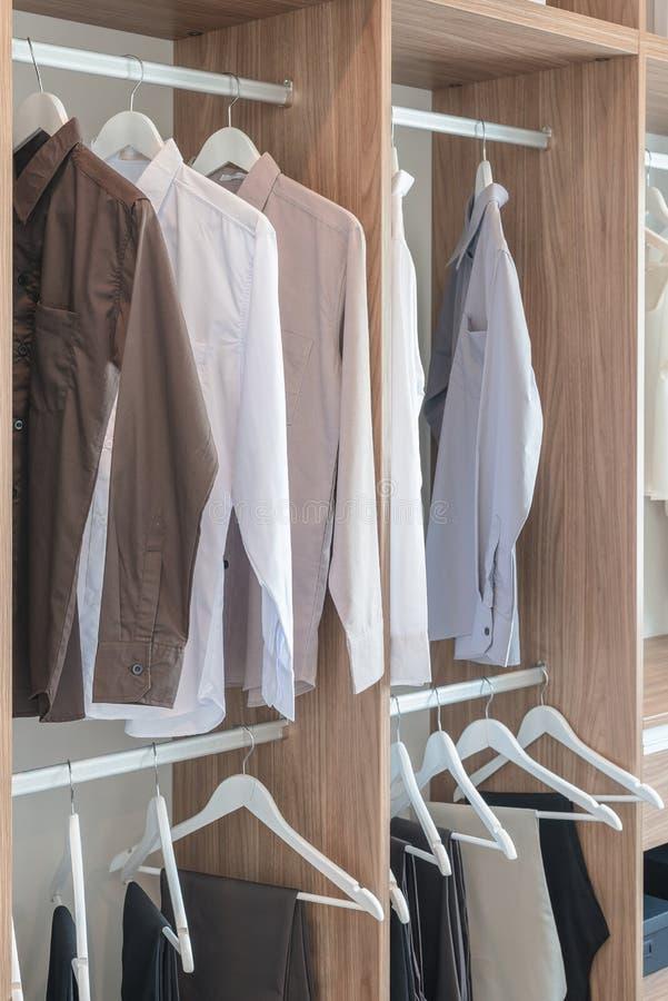 Skjortor och flåsanden som hänger i trägarderob arkivbild