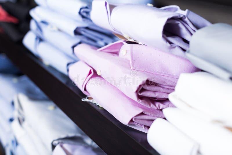 Skjortor på shelfs i manklädlager royaltyfri bild