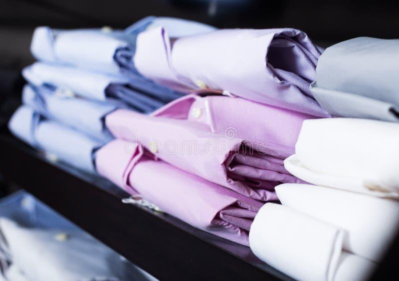 Skjortor p? shelfs i mankl?dlager arkivbild