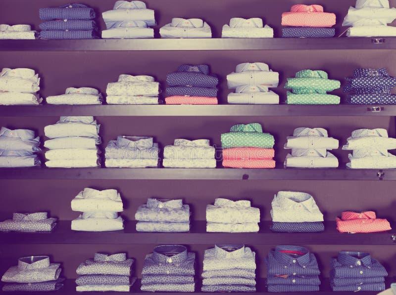 Skjortor p? shelfs i mankl?dlager royaltyfri foto