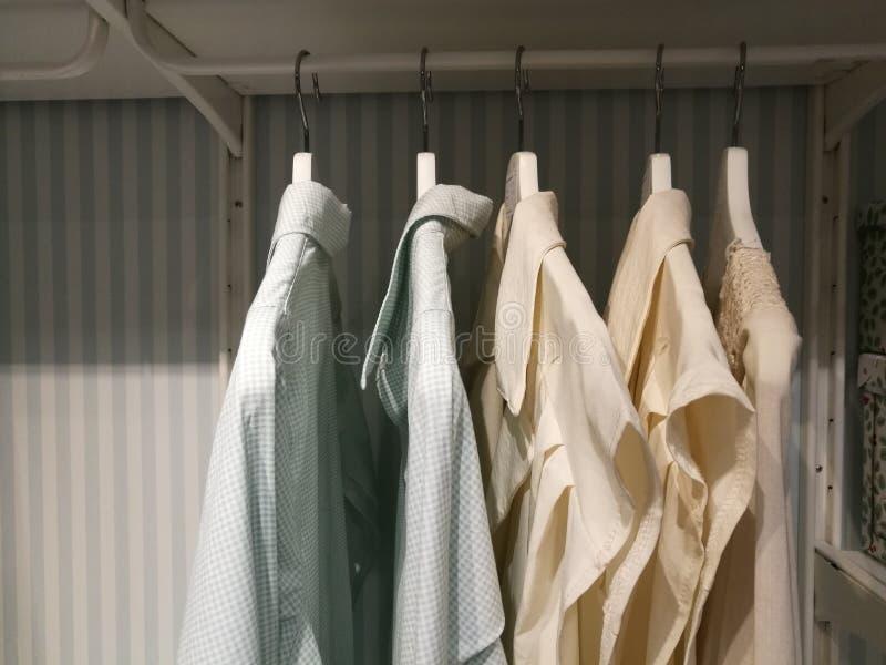 Skjortor som hänger på kuggehängning, fodrar i inbyggt skåp En rad av färgrik kläder som hänger på kuggen royaltyfria bilder