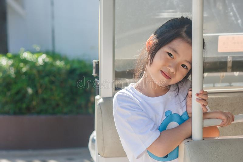 Skjuta den asiatiska lilla gulliga flickan som placerar, i bil och att le för goft royaltyfria foton