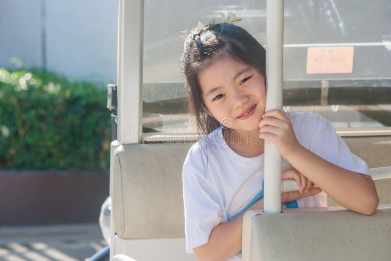 Skjuta den asiatiska lilla gulliga flickan som placerar, i bil och att le för goft arkivbilder