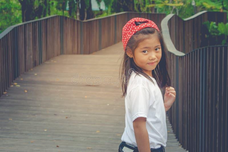 Skjuta det asiatiska gulliga liten flickaanseendet på träwalway och känslig lycka royaltyfria foton
