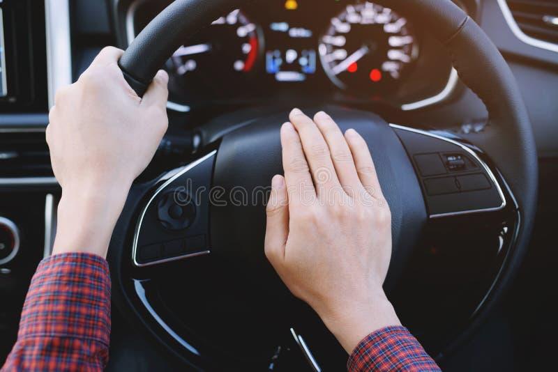 Skjuta för man som är horn-, medan köra sammanträde av en bil för press för styrhjul, royaltyfria bilder
