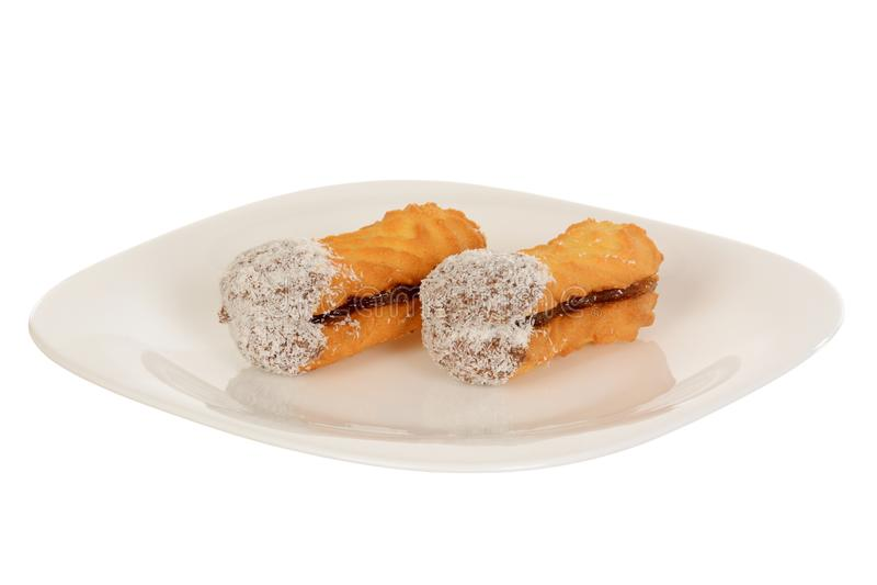 Skjuta in kakor med kokosnöten, ovalen som formas som fylls med chokladpralin arkivbilder