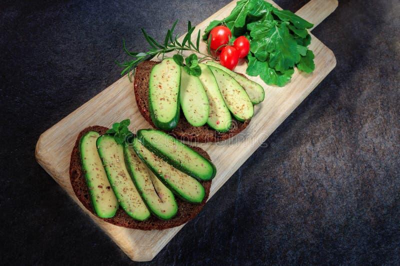 Skjuta in med den kärnfria avokadot, ägget och den körsbärsröda tomaten på skärbrädan Avokadot utan några kärnar ur Coctailavokad arkivfoto