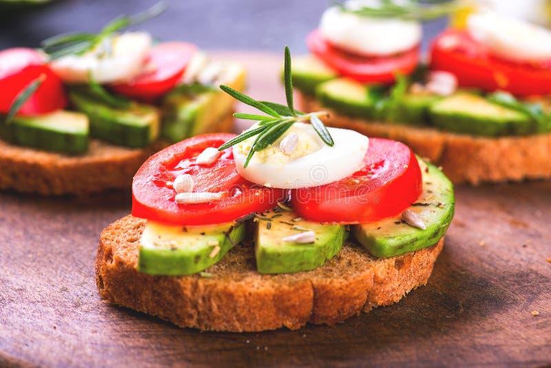 Skjuta in med rågbröd, avokadot, ägget, tomat på träbräde royaltyfri foto