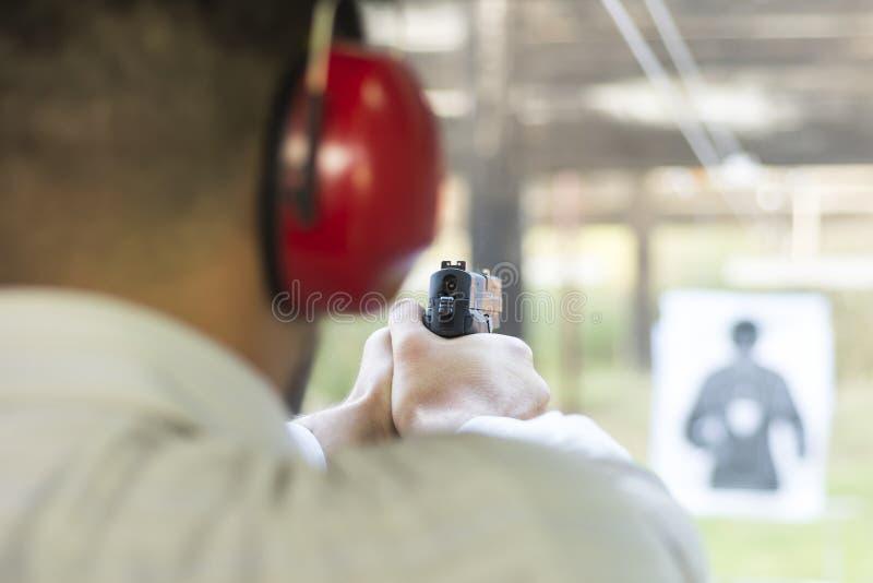 Skjuta med vapnet på målet i skjutbana Skytte för pistol för praktiserande brand för man arkivbild