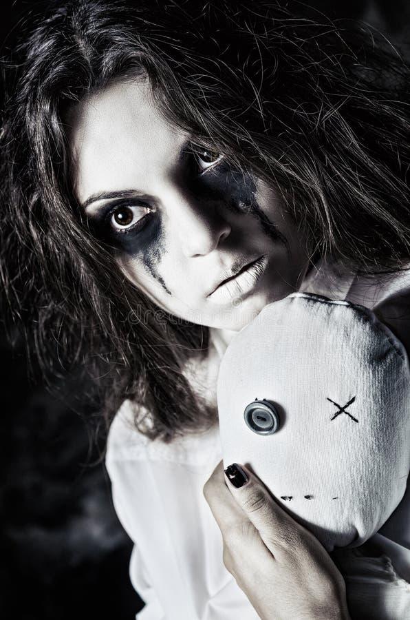 Skjuten fasa: den ledsna konstiga flickan med moppetdockan i händer closeup royaltyfri fotografi