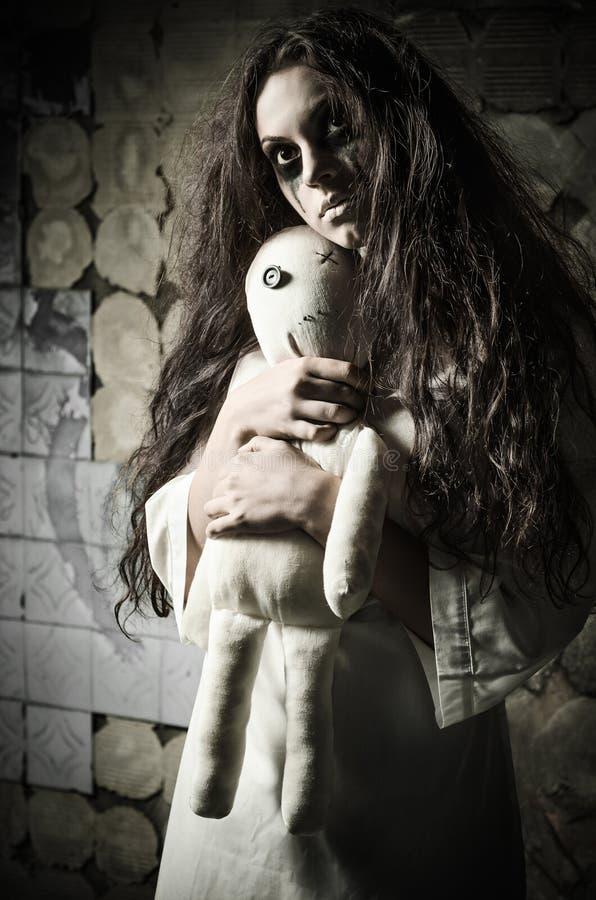 Skjuten fasastil: konstig ledsen flicka med moppetdockan i händer arkivbild